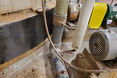 frp wrap repair done in work area with close spaced tank base, pipes and pump